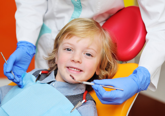 baby boy with blond curly hair dental chair